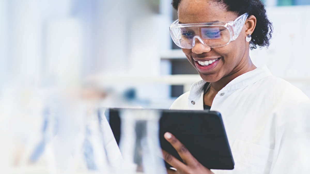 A woman in protective goggles holding a tablet in a lab
