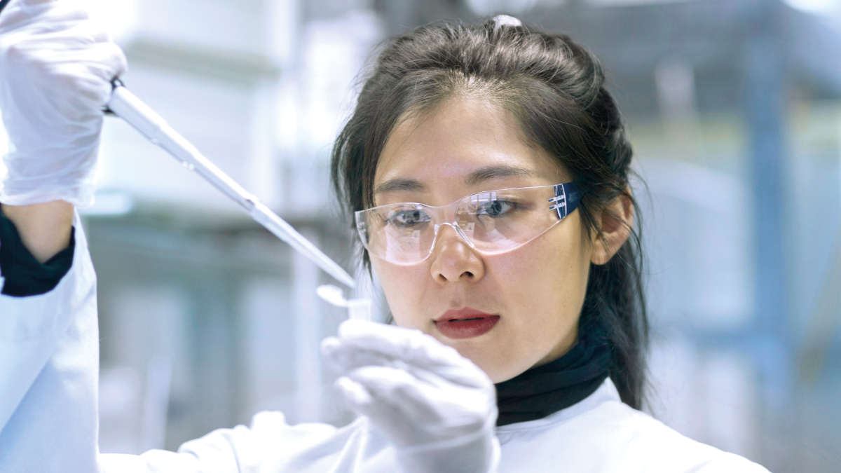 Asian femal scientist, pipetting into a spin tube