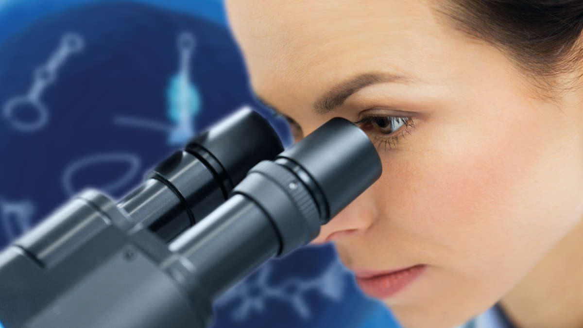 Female scientist view through a microscope