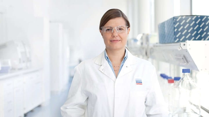 A woman in protective goggles and a lab coat standing in a lab