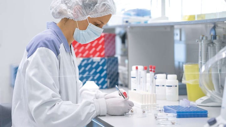 A woman in protective clothing working in a lab