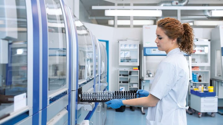 A woman wearing lab coat and blue gloves is working in a lab