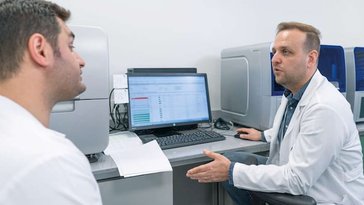 Two scientists in lab coats talking in front of a computer