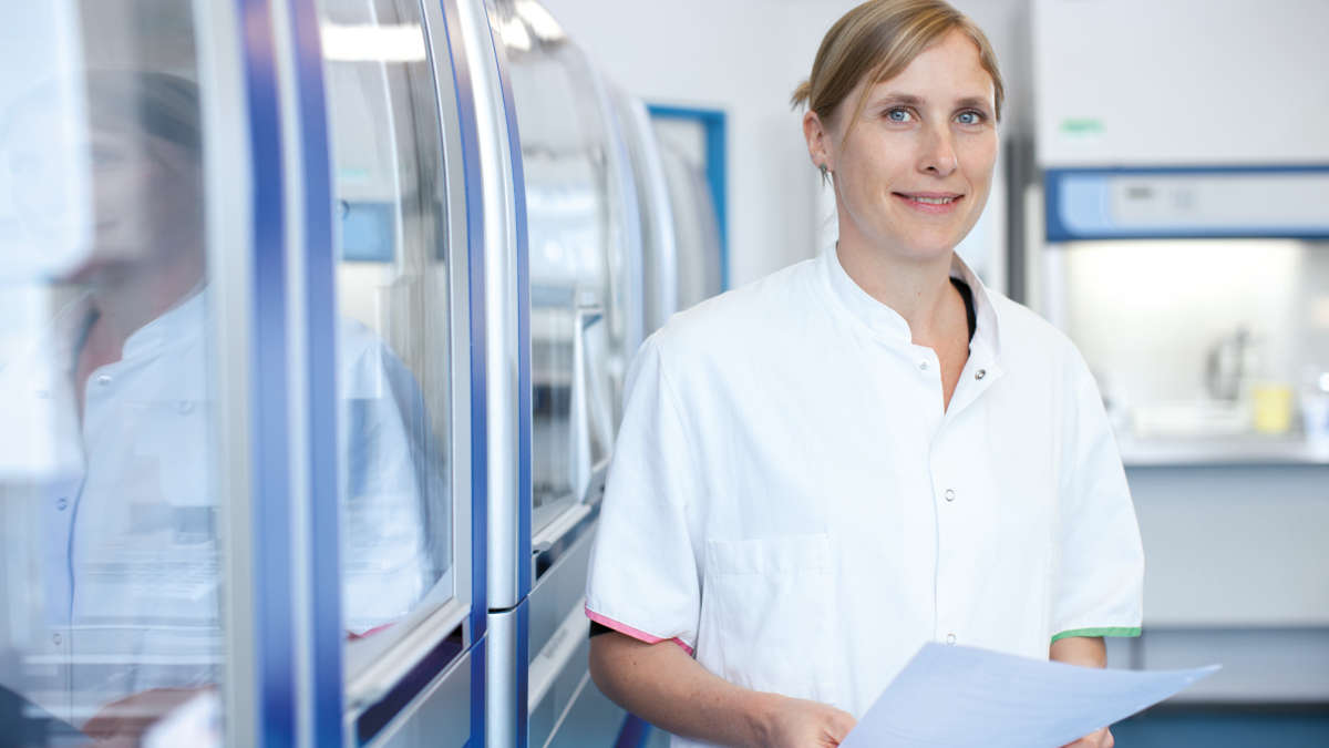 Dr Katja Sanger in a lab is holding a piece of paper