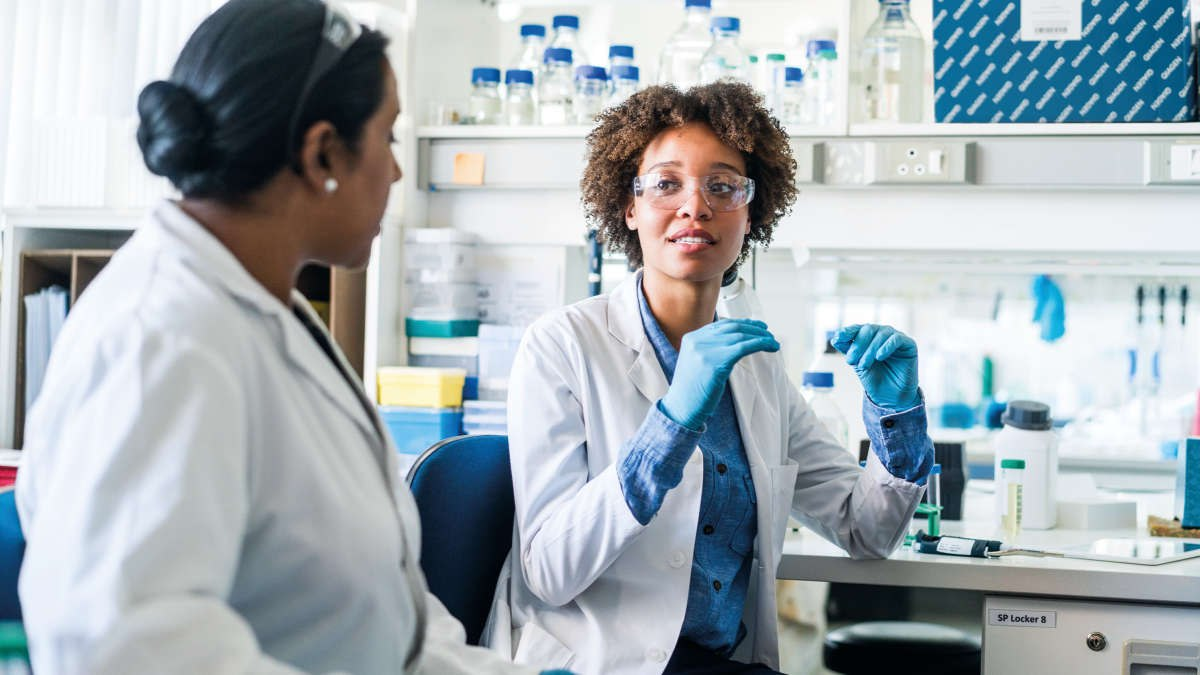 Two female scientists talking in a lab